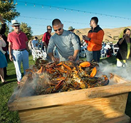 chef with steamer box at outdoor lobster clambake event